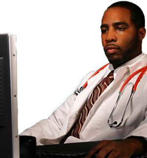 photograph of an African American doctor sitting at a computer and working